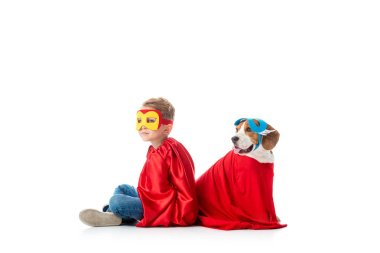 Preschooler child and beagle dog in masks and red hero cloacks sitting back to back isolated on white stock vector