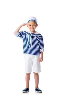 Full length view of smiling preschooler child in sailor costume saluting and looking at camera isolated on white stock vector
