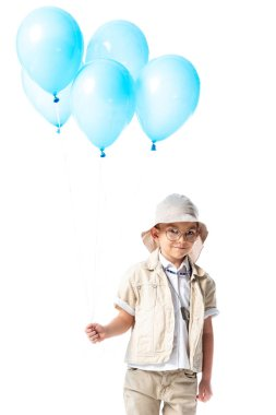 Smiling explorer kid in glasses and hat holding blue balloons and looking at camera isolated on white stock vector