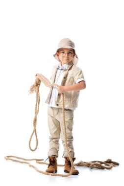 Full length view of explorer kid in hat and glasses holding rope on white stock vector