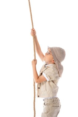 side view of focused explorer kid in hat and glasses holding rope isolated on white