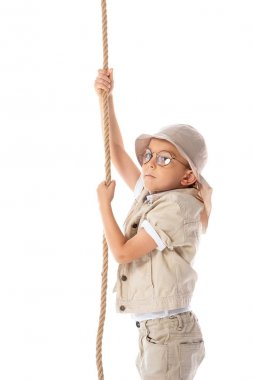 Focused explorer kid in hat and glasses holding rope isolated on white stock vector