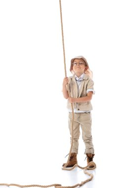 full length view of smiling explorer kid in hat and glasses holding rope on white