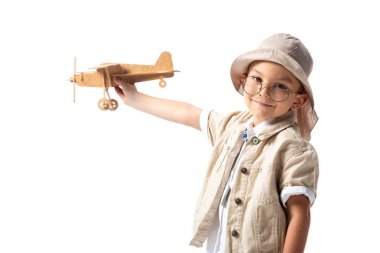 Smiling explorer boy in glasses and hat holding wooden toy plane isolated on white stock vector