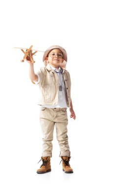 Full length view of smiling explorer boy in glasses and hat holding wooden toy plane isolated on white stock vector