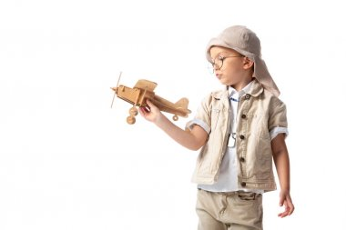 Dreamy explorer boy in glasses and hat holding wooden toy plane isolated on white stock vector