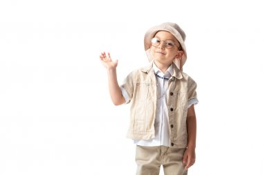 Smiling explorer boy in hat and glasses looking at camera and waving hand isolated on white stock vector