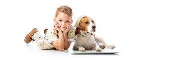 panoramic shot of smiling exploring boy and beagle dog in hat near map on white