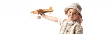 panoramic shot of smiling explorer child in glasses and hat holding wooden toy plane isolated on white