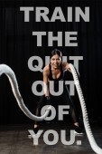 selective focus of sportswoman working out with battle ropes near train the quit out of you letters on black