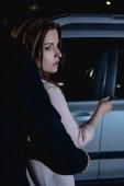 Fotografia ladro attaccando donna da dietro vicino auto di notte
