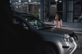 scared woman near car in parking lot at night