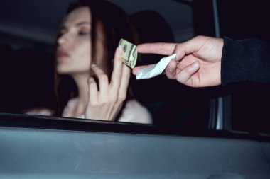 woman in car with dollar banknotes buying drugs from thug