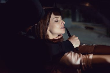 thief attacking beautiful frightened woman in automobile with knife