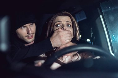 thief strangling beautiful frightened woman in car