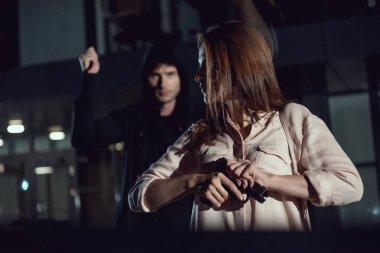 woman holding gun near thief at night
