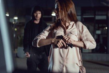 woman with gun near thief at night