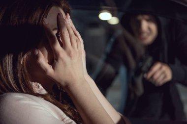 thief pointing gun at woman sitting in car at night