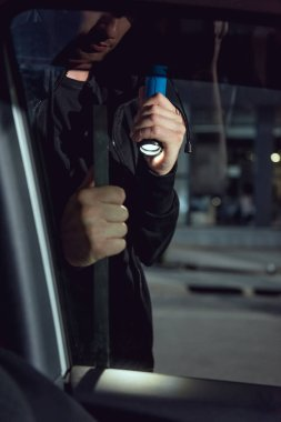 Cropped view of thief intruding car with flashlight and crowbar stock vector
