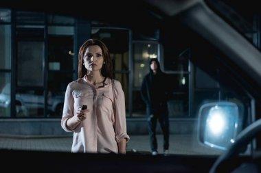 thief following beautiful woman near car at nighttime