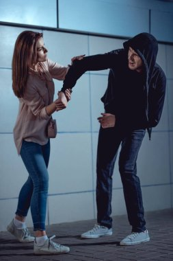 attractive woman fighting with thief in underpass