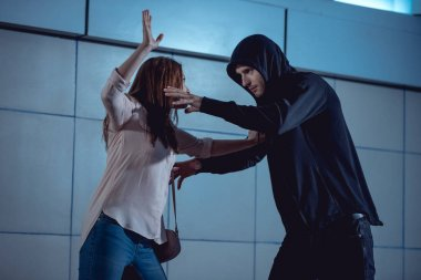 Woman defending herself from attacking thief in underpass stock vector