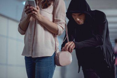 Thief stealing money from bag of woman using smartphone stock vector
