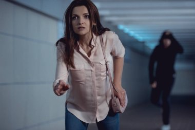 beautiful woman running from thief in underpass