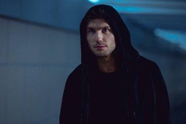 handsome thief in black hoodie in underpass