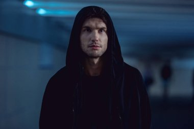 selective focus of handsome thief in black hoodie in underpass