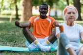 Photo selective focus of retired african american man with closed eyes sitting with crossed legs near senior woman in park