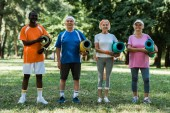 happy retired and multicultural pensioners holding fitness mats while standing on green grass in park