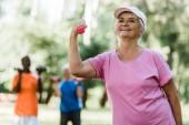 selektivní zaměření šťastné ženy v důchodu v čepici držené při cvičení v blízkosti důchodců