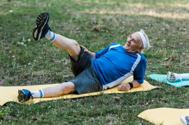 senior man with grey hair training on fintess mat in park
