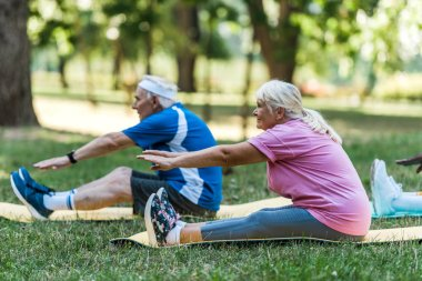 selective focus of senior woman with grey hair and man working out on fintess mats on grass