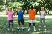 cheerful multicultural pensioners in sportswear exercising with dumbbells in park