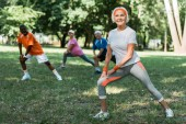 selective focus of cheerful retired woman stretching near multicultural pensioners on grass