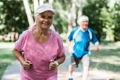 selektivní zaměření šťastné ženy v důchodu v čepici běžící poblíž staršího muže v parku