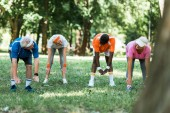 selective focus of multicultural pensioners doing stretching exercise on grass