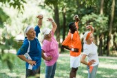 selective focus of cheerful multicultural retired men and women standing with hands on hips while doing exercise