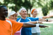 selective focus of happy retired man standing with outstretched hands near multicultural pensioners in park