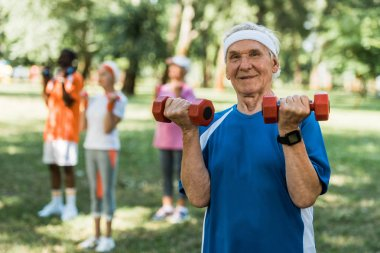 selective focus of happy senior man holding dumbbells in park