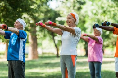 selective focus of senior pensioners exercising with dumbbells in park