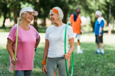 selective focus of cheerful senior women smiling while holding hula hoops