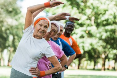selective focus of cheerful retired woman near multicultural men and woman doing stretching exercise