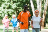 selective focus of african american senior man and happy retired woman exercising near pensioners outside