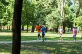 selective focus multicultural and senior men and women in sportswear jogging in park