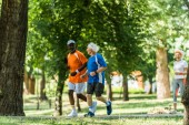 Photo selective focus of happy multicultural men running with retired woman