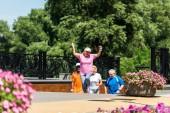 selektiver Fokus der glücklichen Rentnerin feiert Triumph in der Nähe von multikulturellen Rentner na-Park