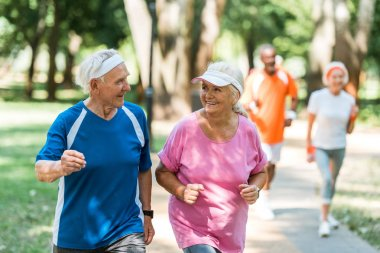 selective focus of positive senior couple exercising outside